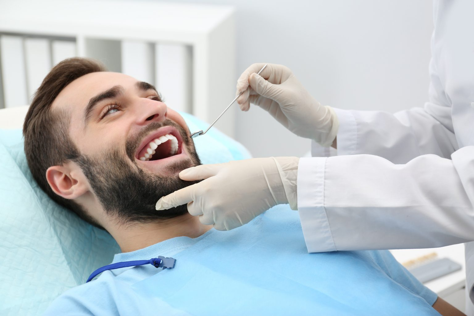 Dentist Examining Young Man's Teeth With Mirror In Hospital